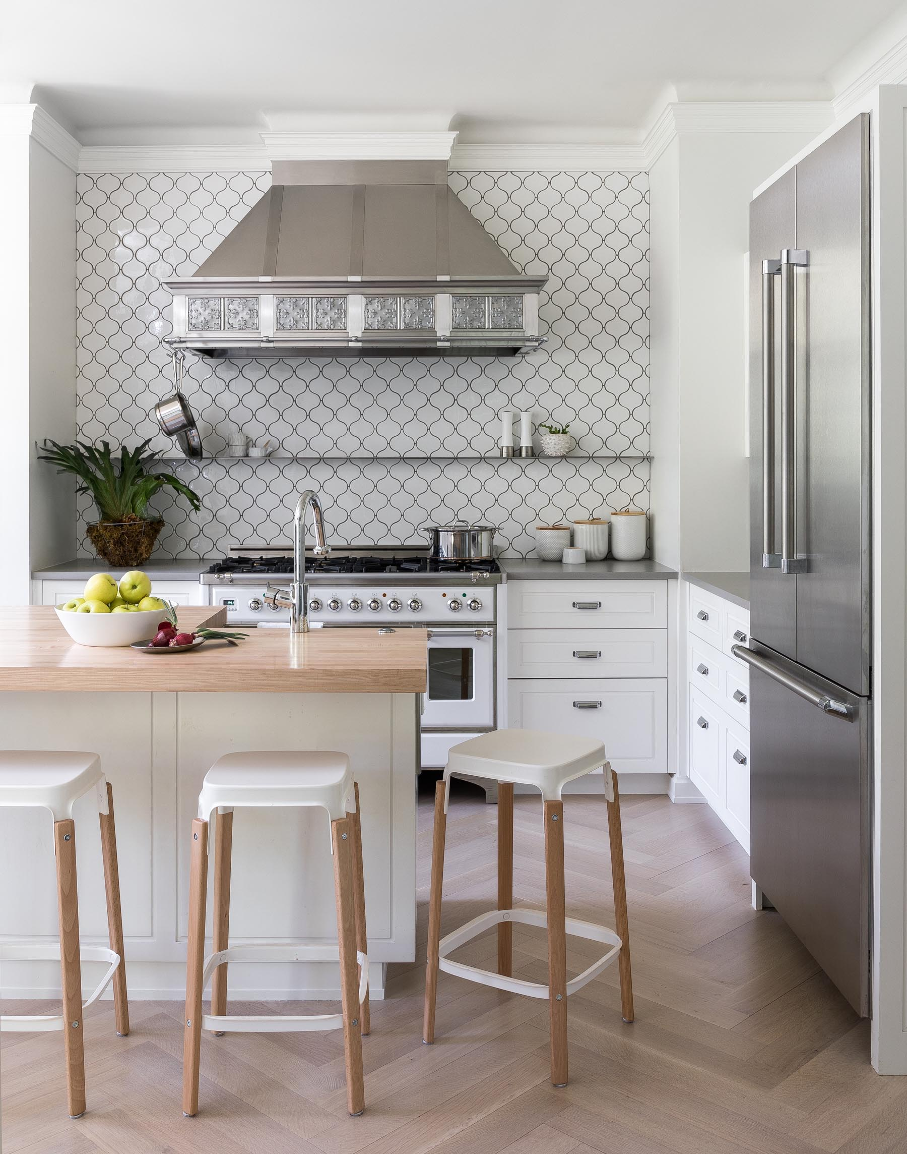 In this remodeled kitchen, there's wood flooring in a herringbone pattern, white cabinets, a patterned white tile with dark grout, and stainless steel appliances. An island with a wood countertop complements the flooring.