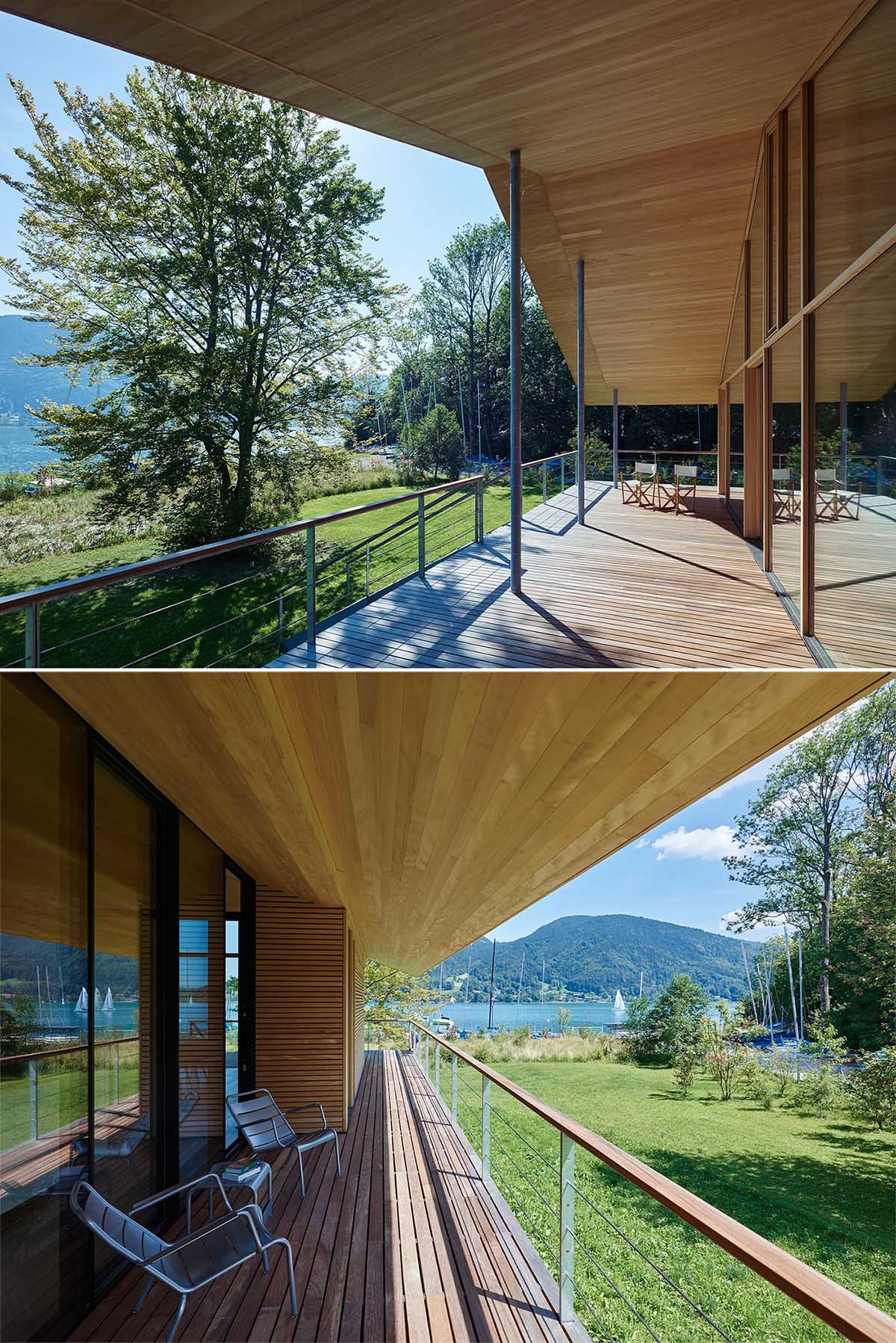 A wooden walkway surrounds this modern house and widens into a terrace at the lakeside, completely covered by the steep saddleback roof.
