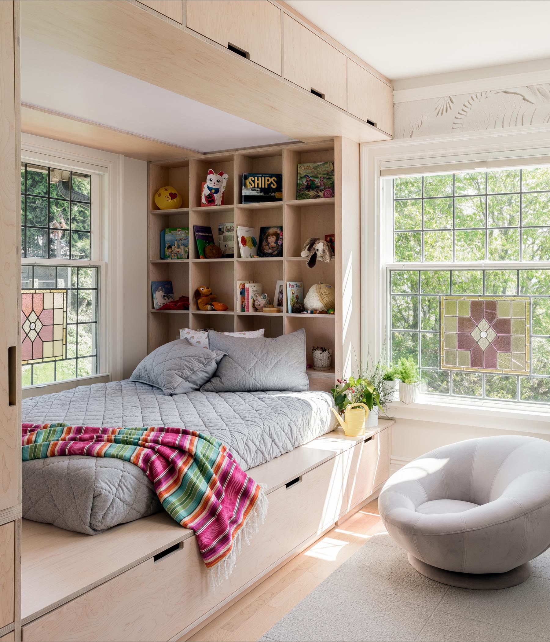 A custom wood bed design has plenty of storage including cabinets, drawers, and open shelving.