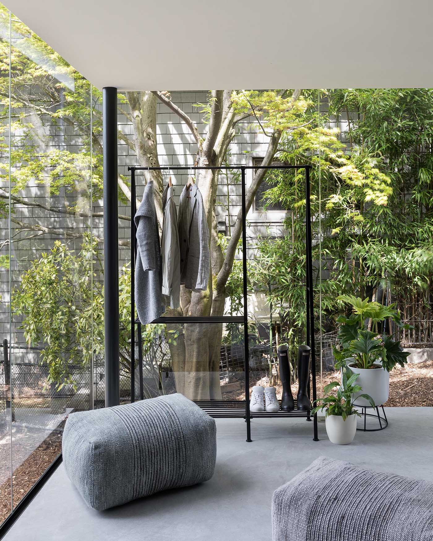 This updated light filled home has a new glass enclosed entryway with black frames, creating a contemporary addition to the brick and wood house.