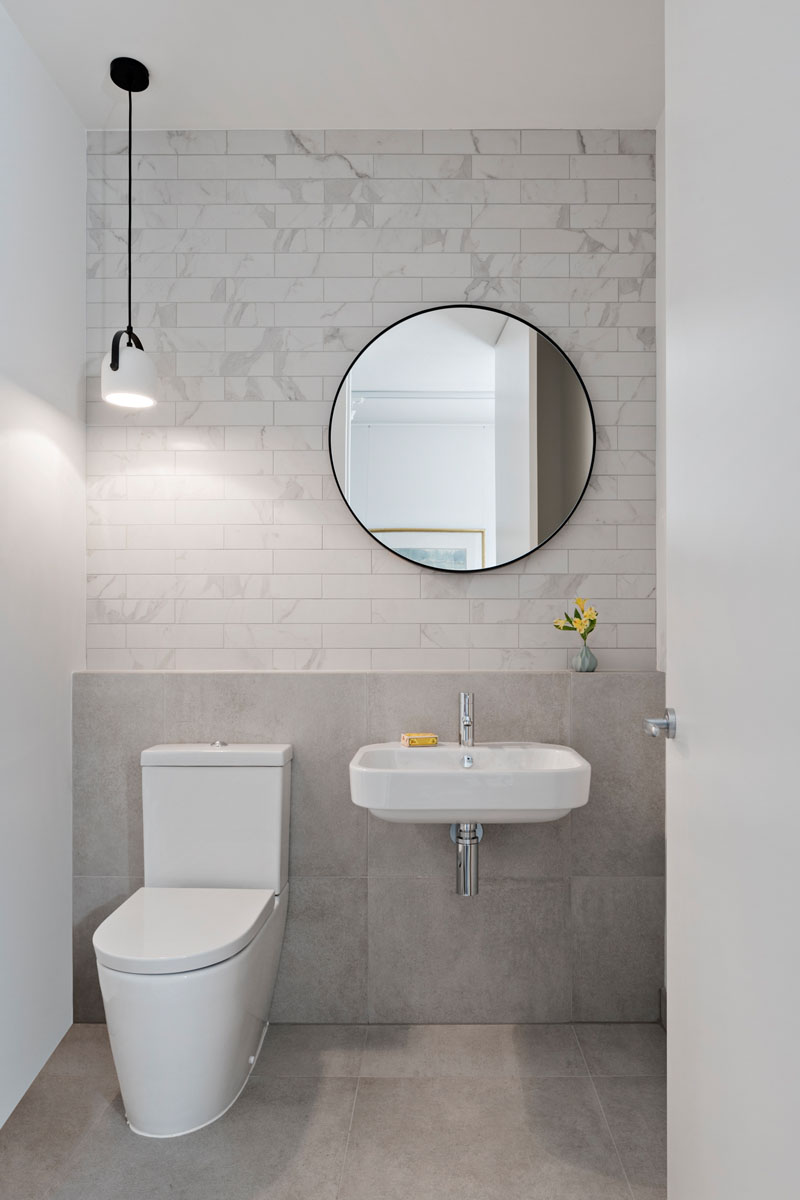 This minimalist bathroom includes white and light grey tiles that line the back wall, while a single white and black pendant light hangs above the toilet.