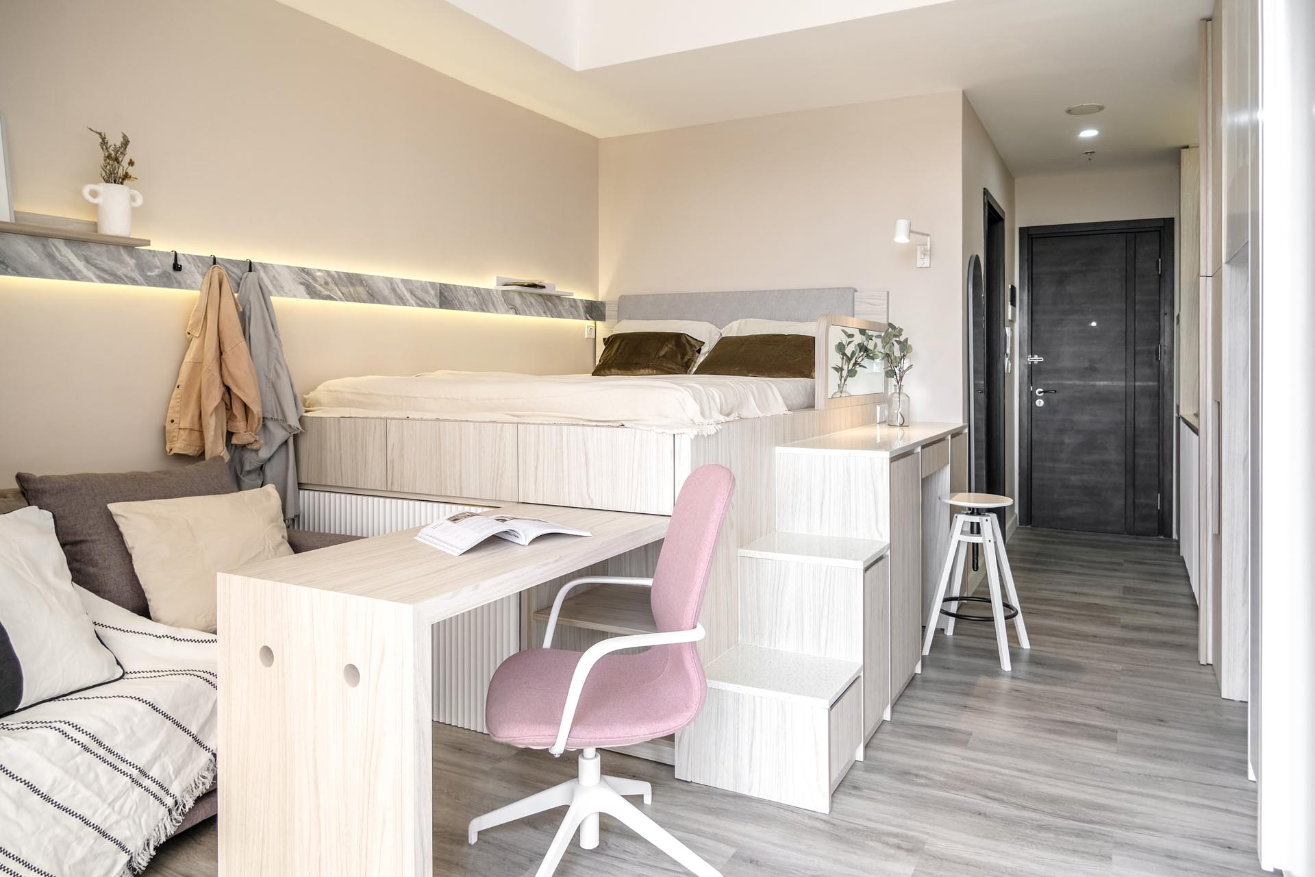 A small apartment with a loft bed includes a home office, storage, and hidden lighting.