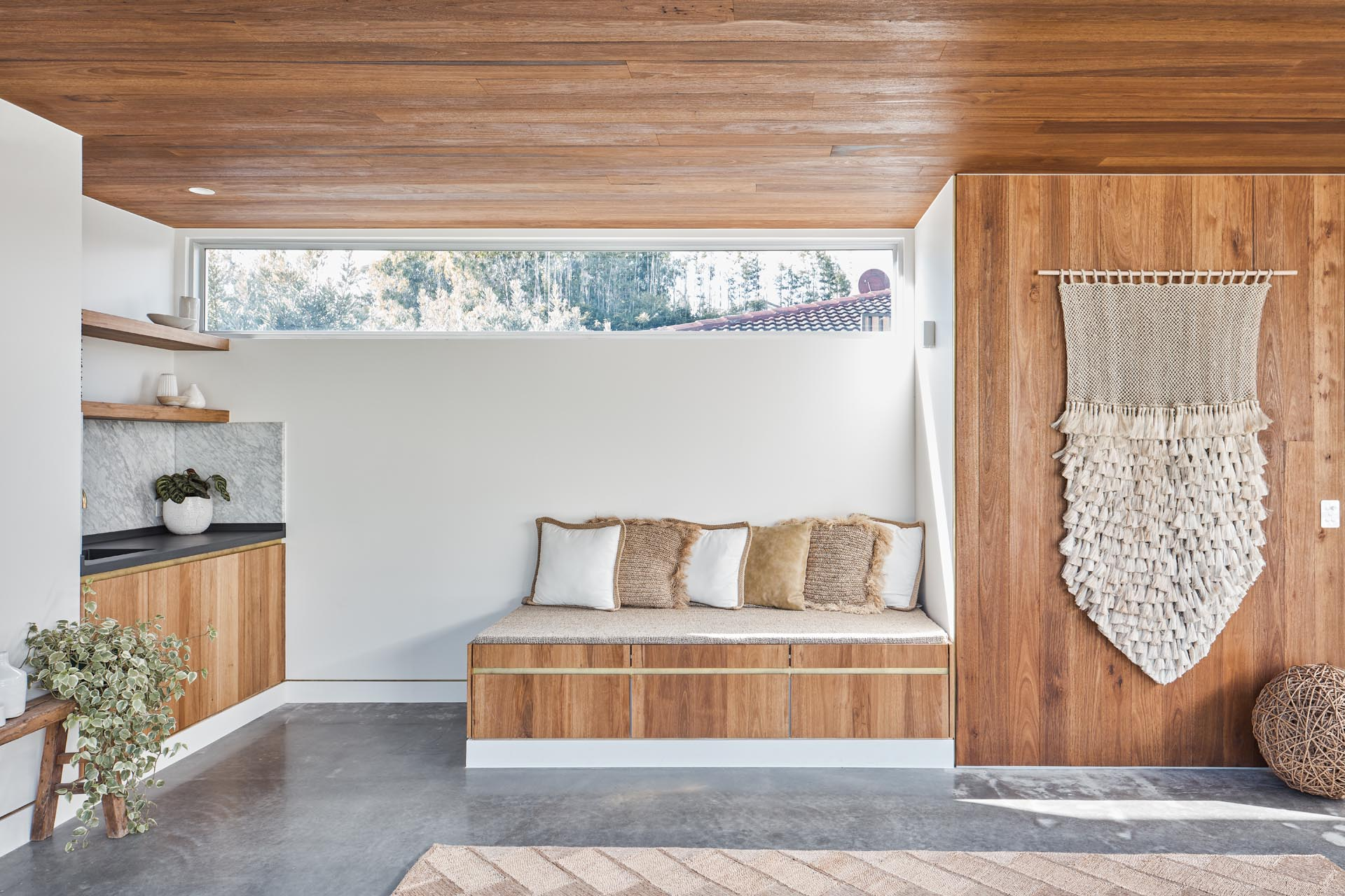 With mid-century modern influences, the sliding glass walls of this backyard studio, seamlessly open the interior spaces of the studio to the backyard. Inside, there's a wood ceiling, polished concrete floors, a small bench, storage, and a kitchenette.