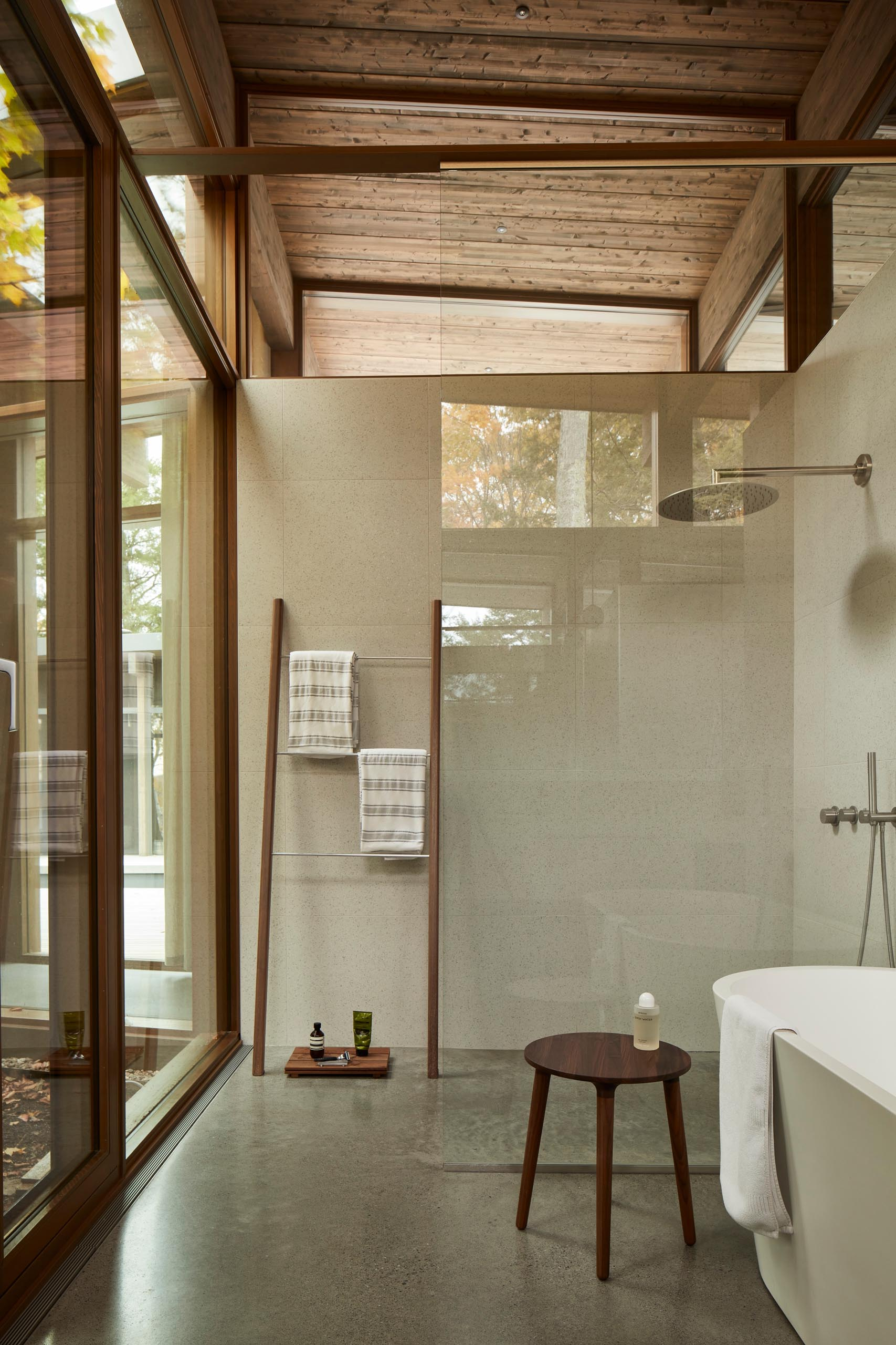 In this minimalist bathroom, wood accents have been added in the form of a decorative ladder, tray, and stool.