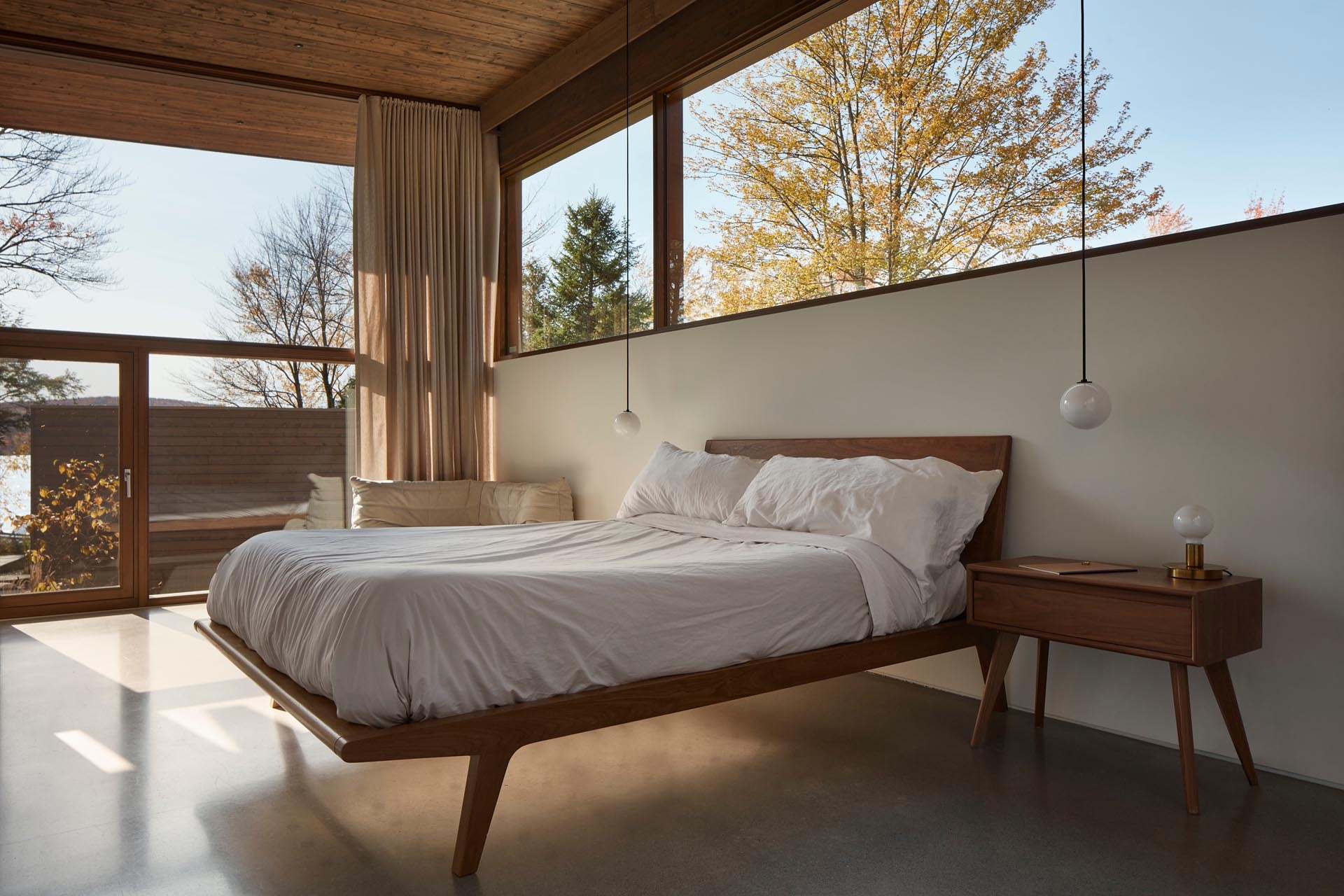 A modern bedroom with a concrete floor and a wood bed frame with matching side tables.