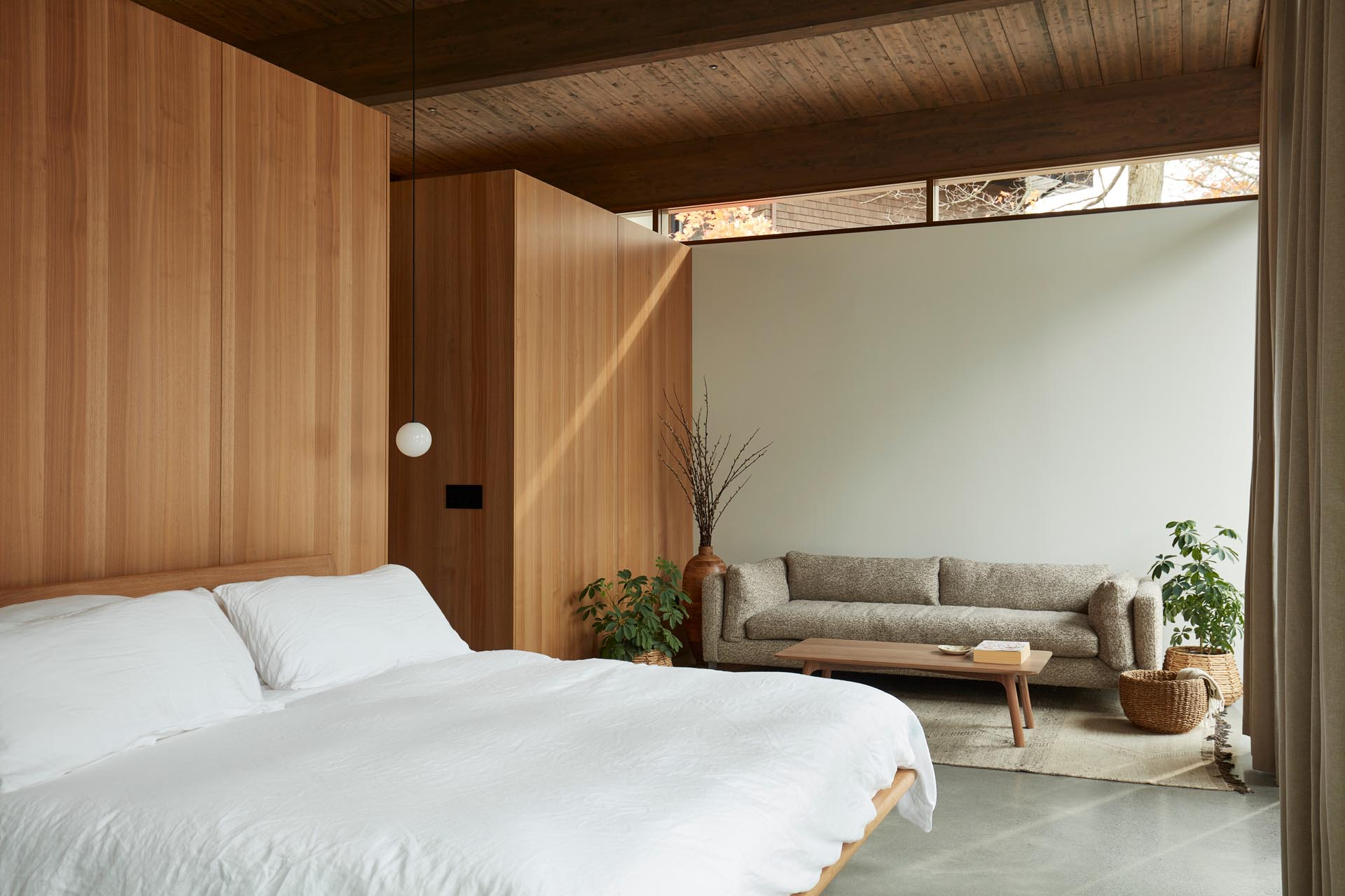 In this modern bedroom, custom wood closets serve as the backdrop for the bed.