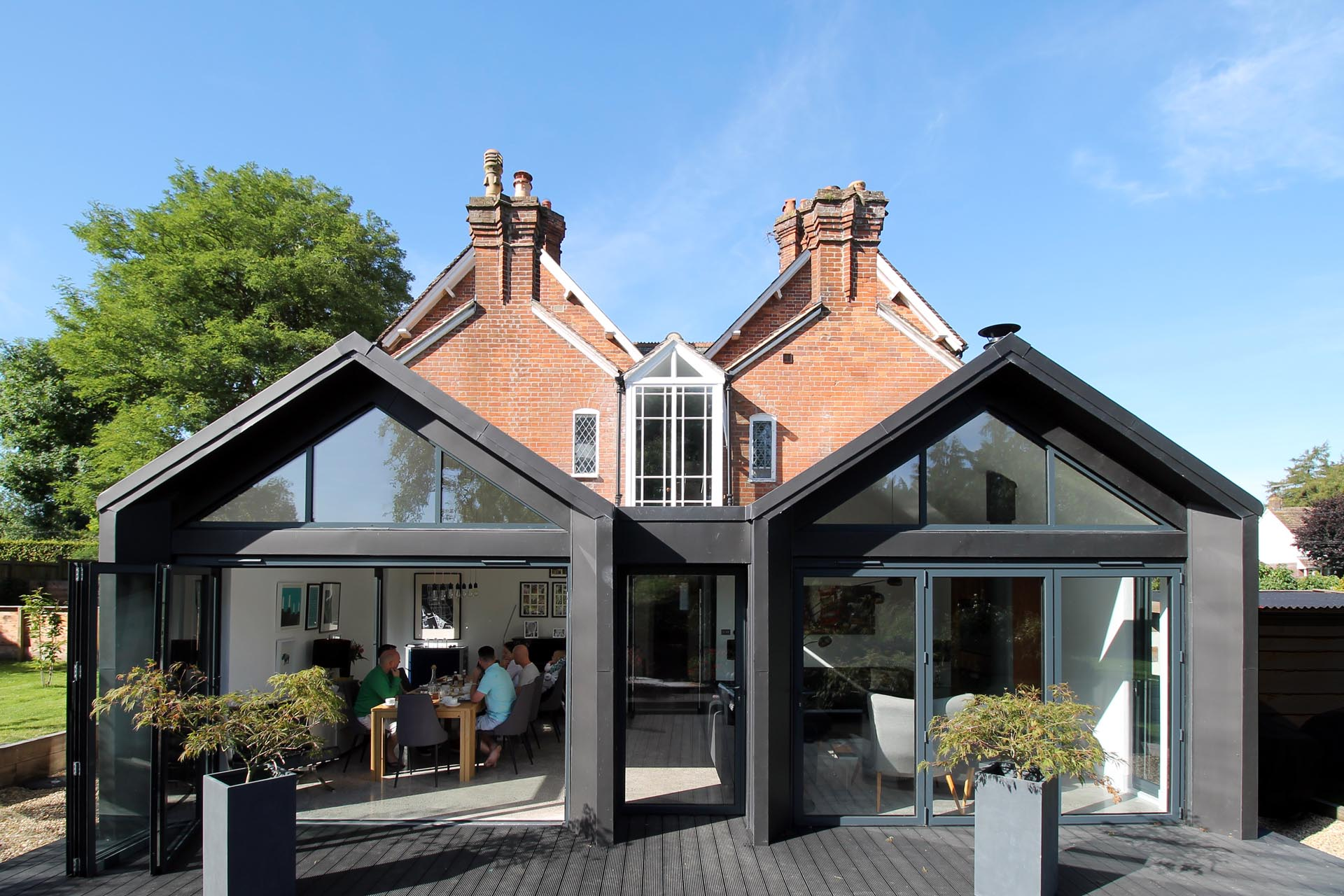 A modern extension with pitched roofs and black in black zinc.
