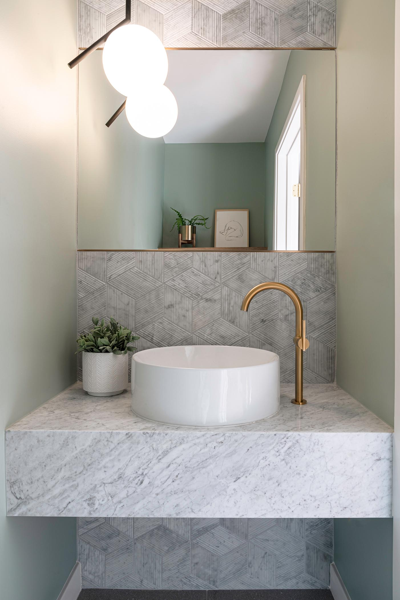 A powder room that showcases Salvatori Romboo tile with a textural bamboo-like finish, while a floating vanity is topped with a round white vessel sink from KOHLER and bronze accents from Newport Brass.