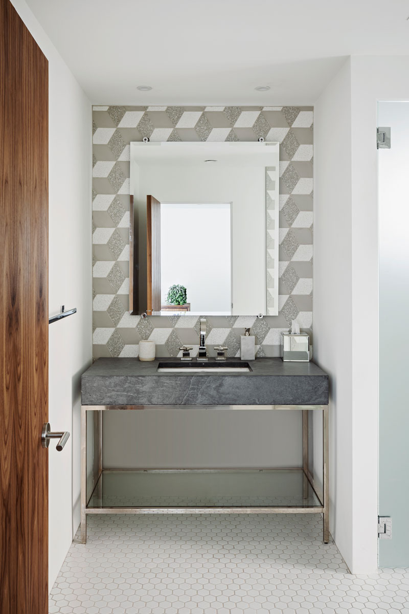 In the powder room of a remodeled house by The Ranch Mine, decorative geometric tiles cover the wall, while a simple vanity with chrome accents adds a touch of glamour.