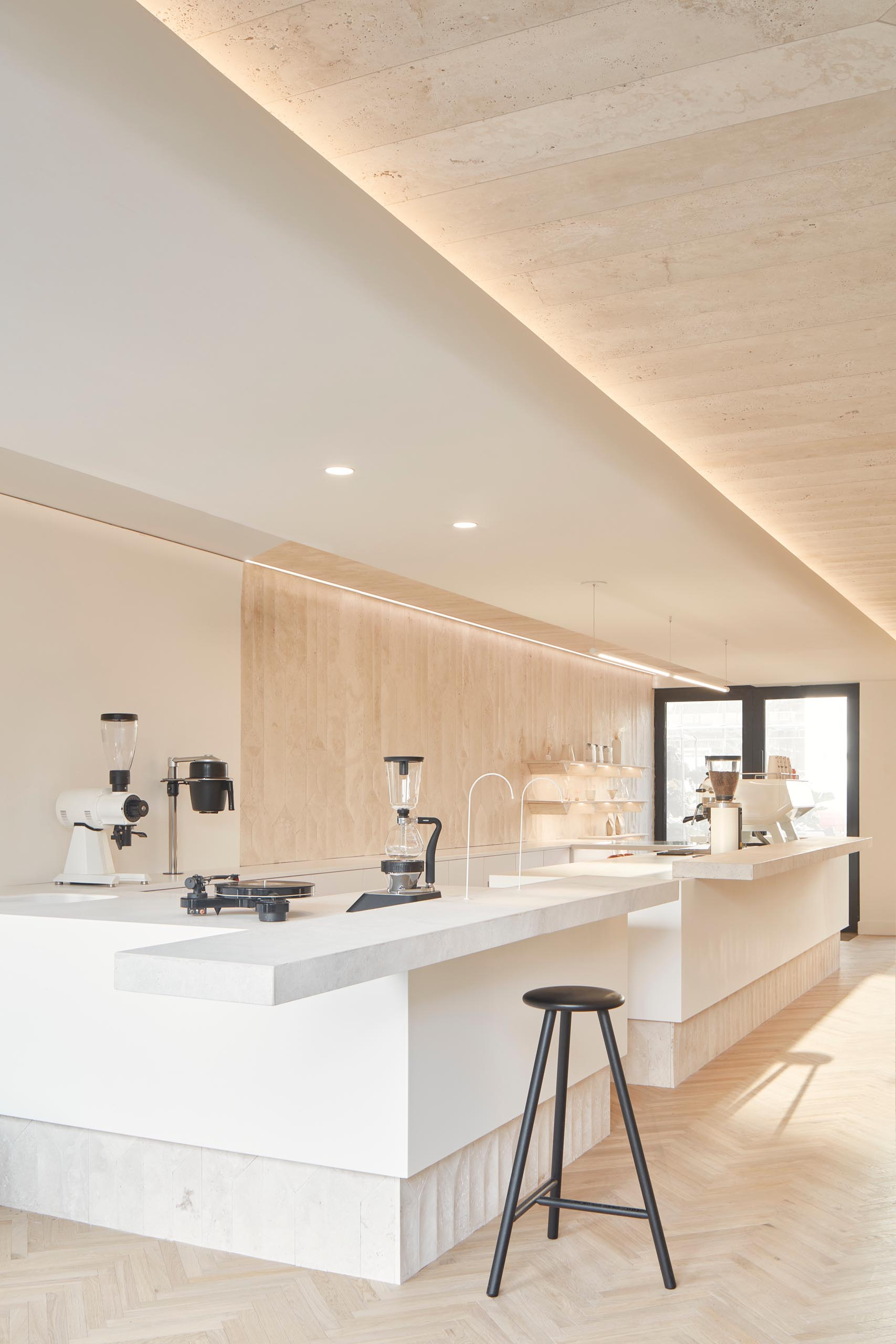 A modern coffee shop inside a shipping container has a large bar, herringbone wood floors, and travertine walls.