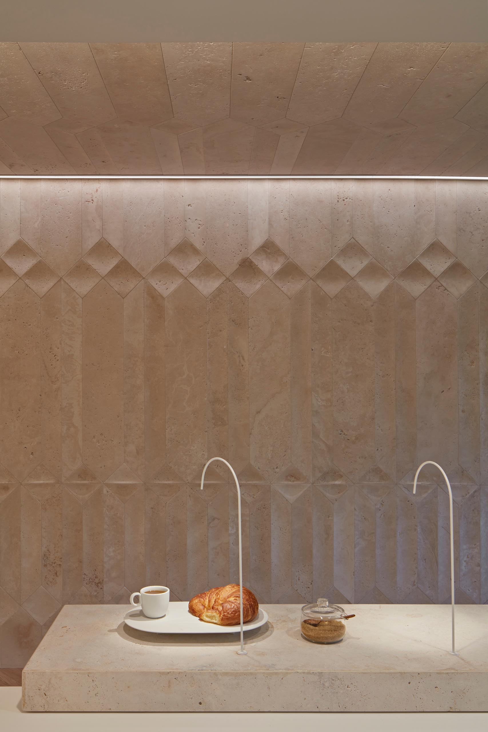 Custom designed travertine walls create unique shadows inside a coffee shop.