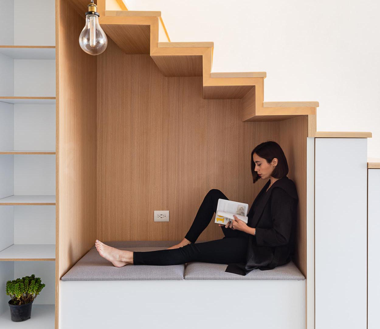 An under-stair wood lined nook has bench seating with an upholstered cushion, as well as an outlet and a nearby pendant light. To the left of the nook is an open shelving unit, while to the right, are small cabinets.