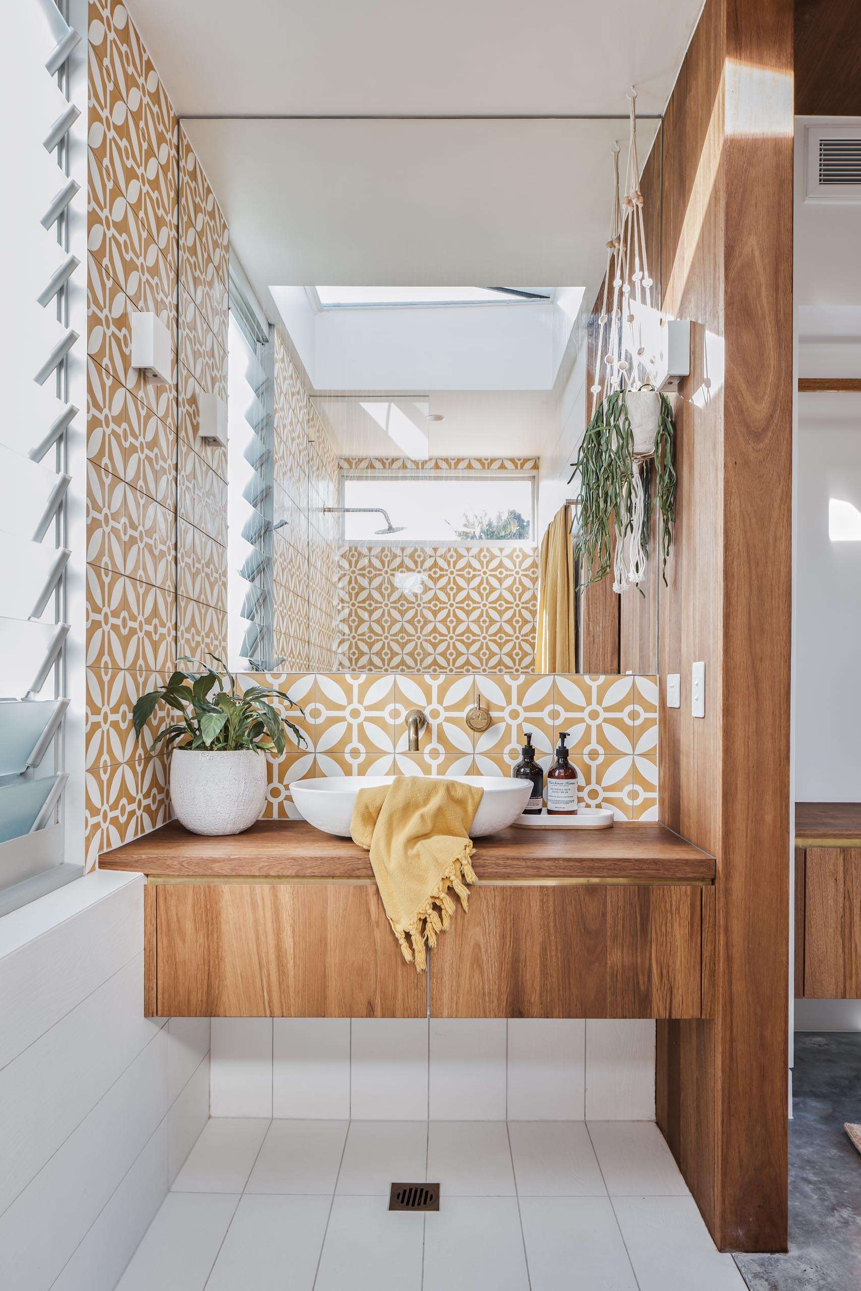 This modern en-suite bathroom includes patterned tiles, a warm wood vanity, and a walk-in shower.
