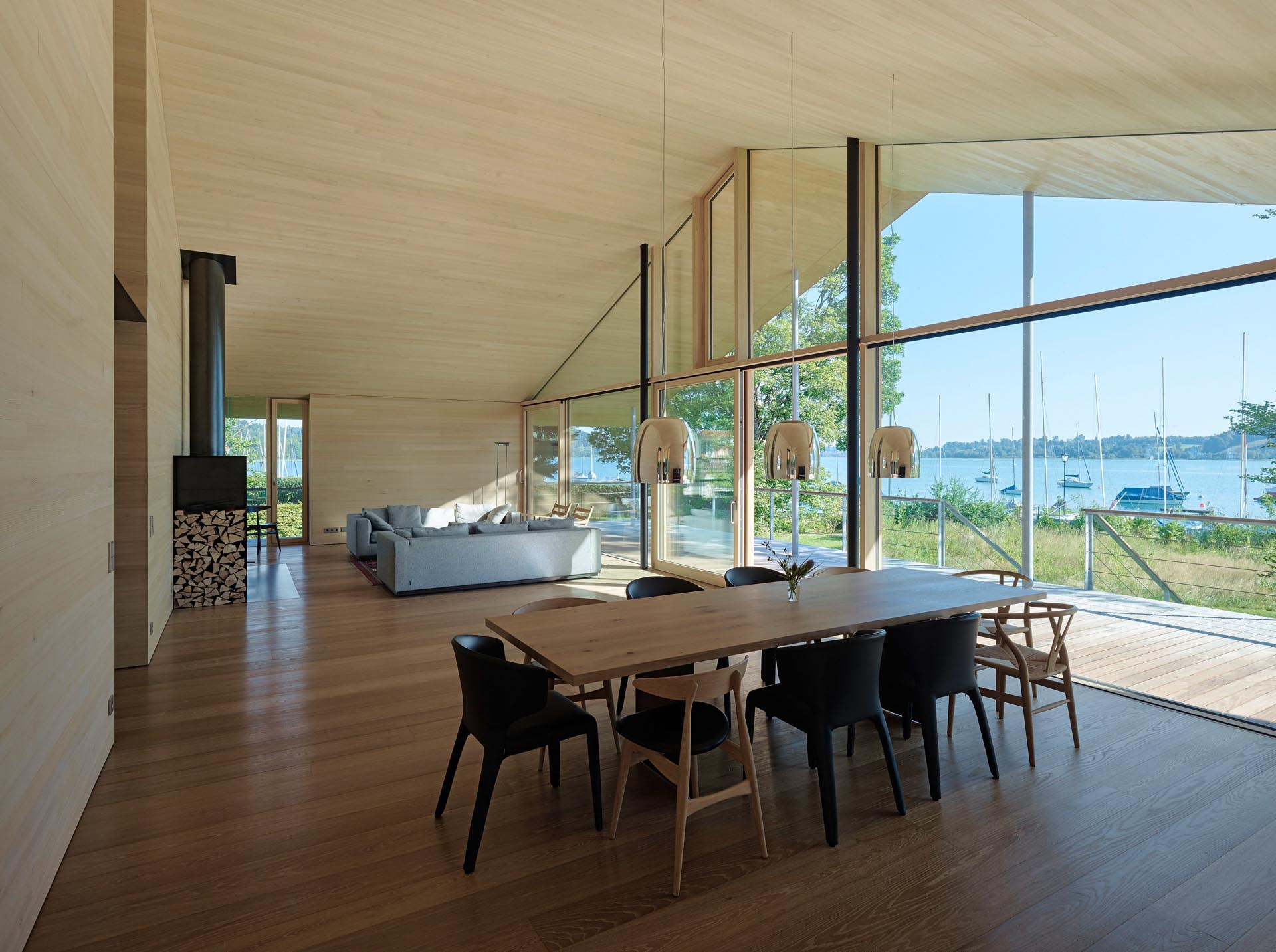 An open plan living room and dining room showcases a full wall of windows that look out to the lake and boats.