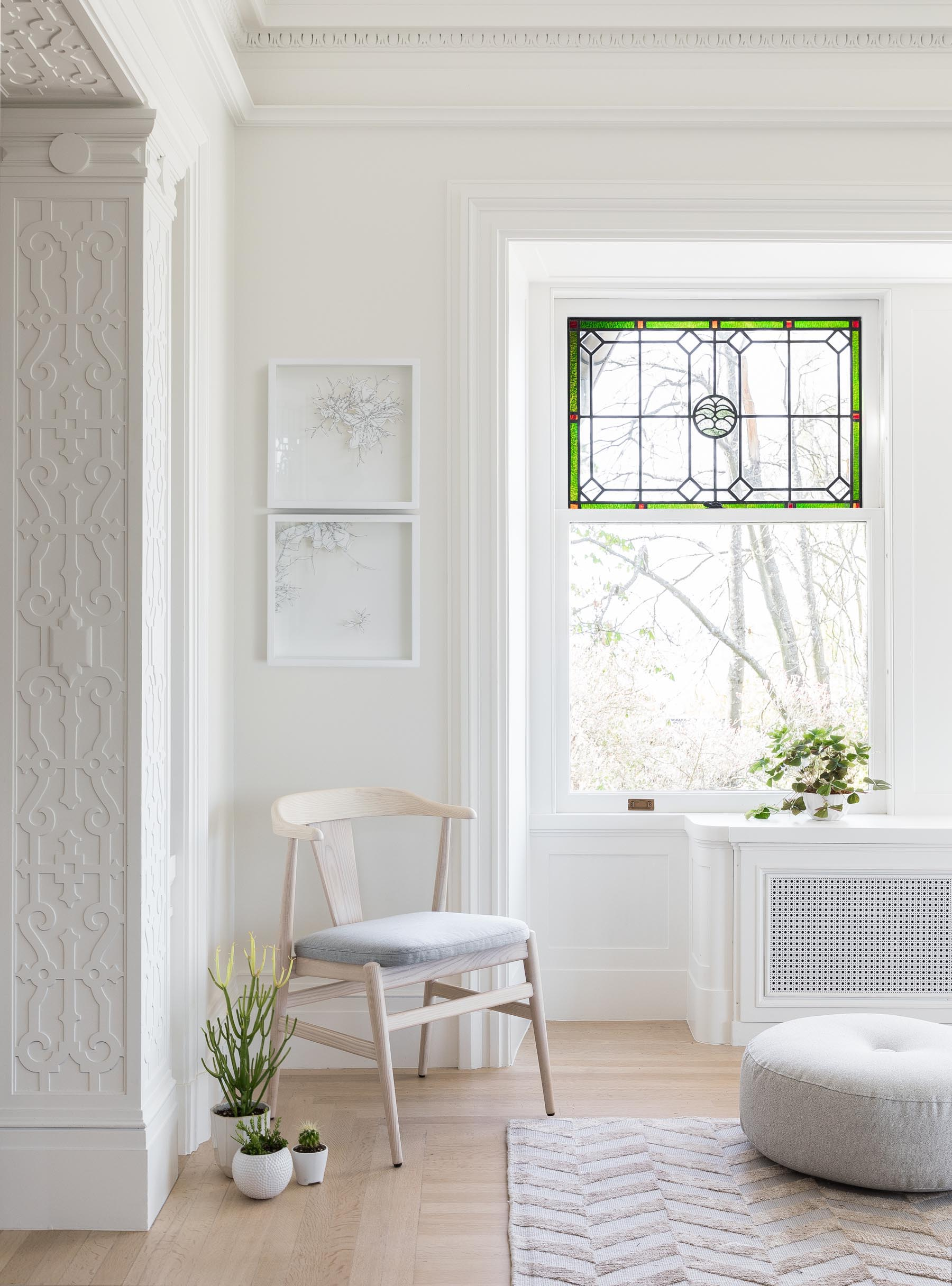 Stained glass windows provide the mostly white interior a pop of color, while light wood and gray tones are used in the furniture choices.