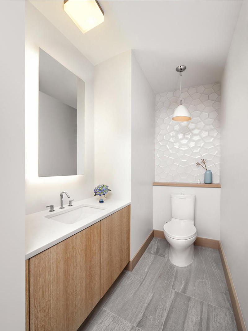 A small bathroom with accents of textured tile and wood.