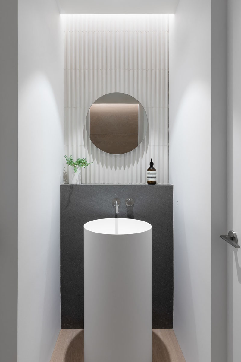 A powder room in a small house designed by Falken Reynolds Interiors and Randy Bens Architect, includes a pedestal sink and faucet, a Basalt ledge, and Mutina tile on the wall.