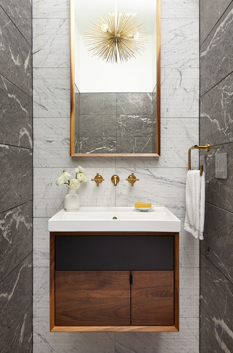 A powder room that has a few brass accents and a tall mirror to brighten up the small space.