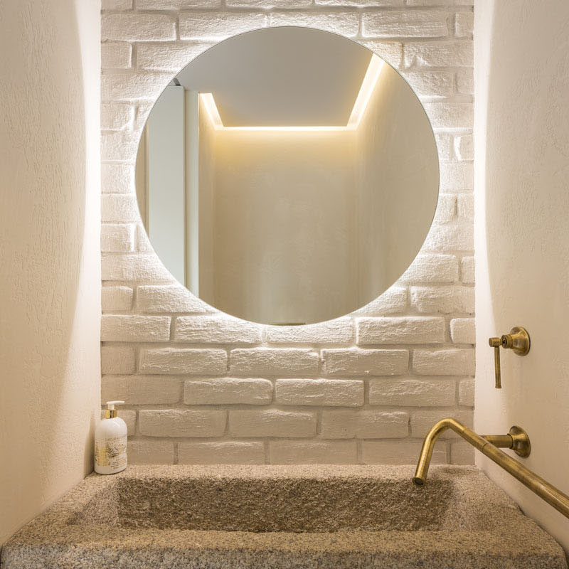 A small powder room with a reclaimed granite trough as the sink and a backlit mirror.