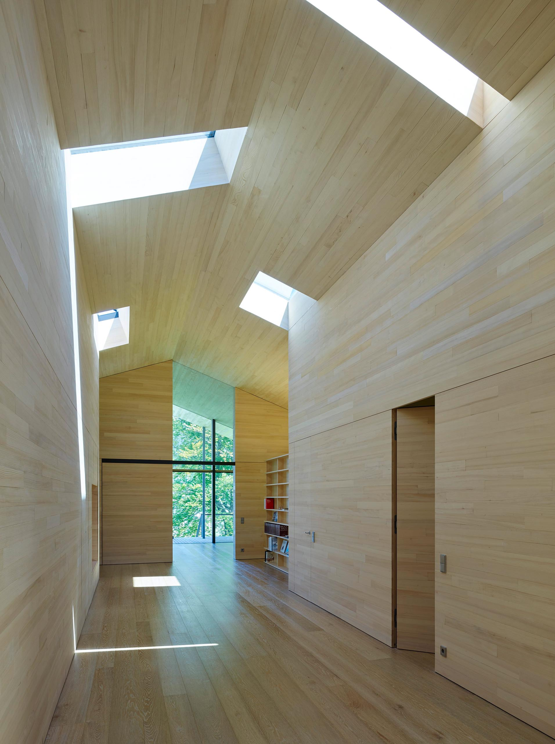 Inside this home, wood lines the walls, floor, and ceiling, while skylights brighten the hallway leading from the door to the social areas.