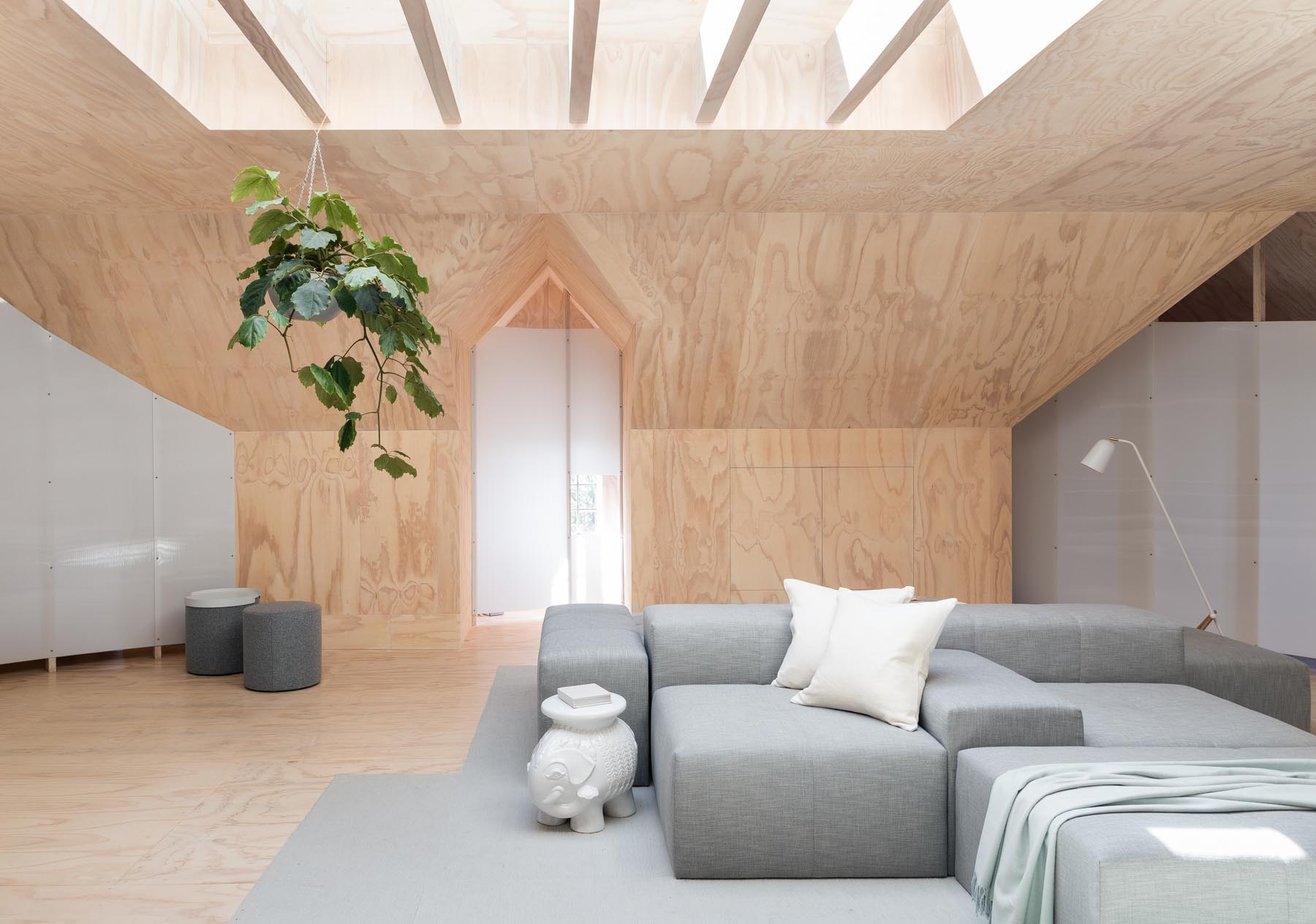 A plywood lined attic with skylight and living room.